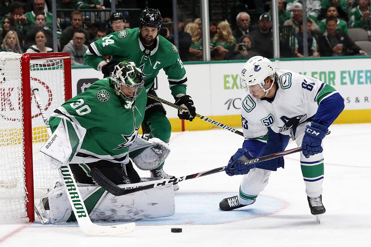 Dallas Stars goaltender Ben Bishop (30) and left wing Jamie Benn (14) defend the net against a shot by Vancouver Canucks center Jay Beagle (83) in the second period of an NHL hockey game in Dallas, Tuesday, Nov. 19, 2019. (AP Photo/Tony Gutierrez)